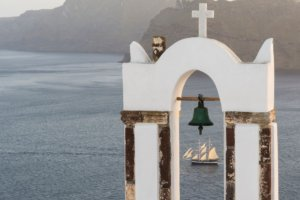 Traditional church belfry and sailing boat at sunset in Oia, Santorini, Greece