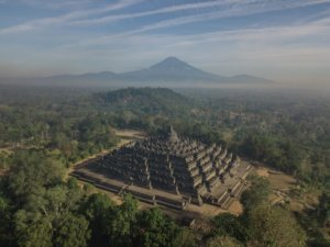 A misty morning at the Borobudur Temple with volcanoes in the background