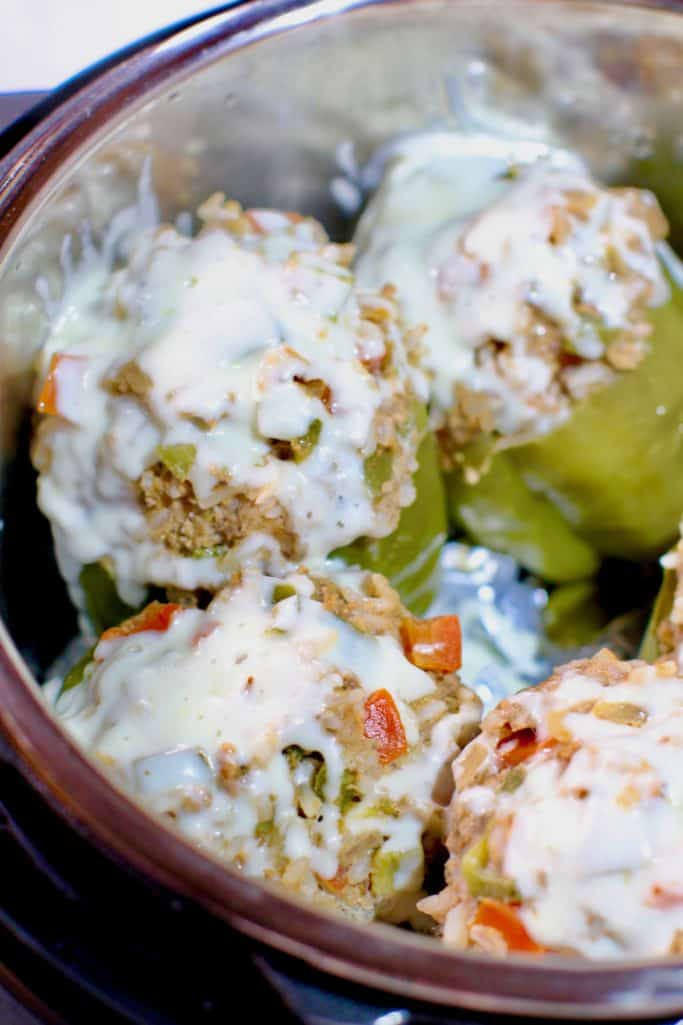 ground beef stuffed green bell peppers in an Instant Pot electric pressure cooker with melted mozzarella cheese on top