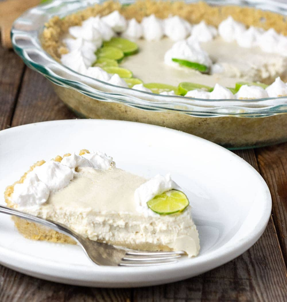 Best vegan key lime pie slice with a fork on a white plate in the foreground and pie plate with pie in the background made with cashews, coconut cream, maple syrup in a graham cracker crust, garnished with coconut whipped cream, key lime pie slices on a wooden background with key limes on a burlap napkin