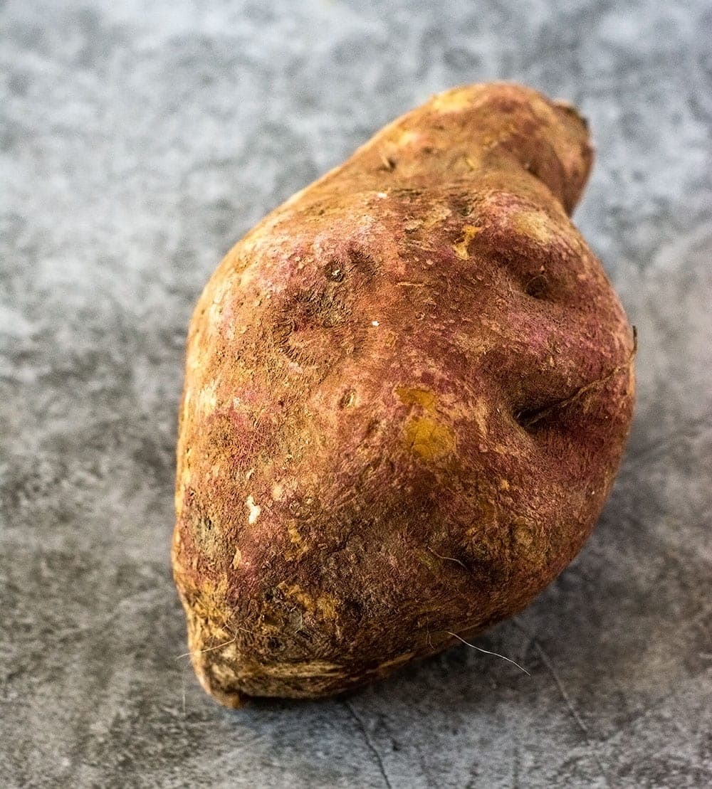 Whole sweet potato on a grey background