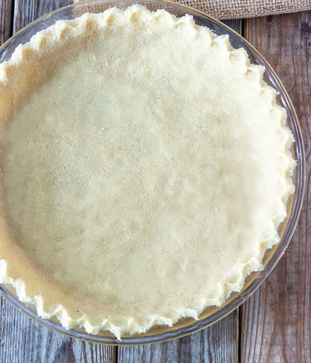 almond flour pie crust in prepared pie plate before baking
