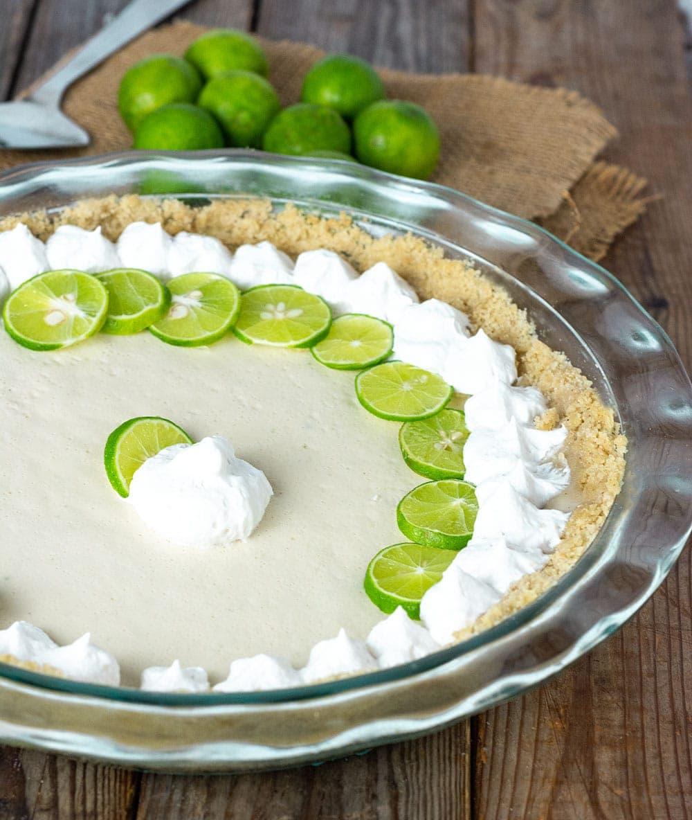Dairy free key lime pie made with cashews, coconut cream, maple syrup in a graham cracker crust, garnished with coconut whipped cream, key lime pie slices on a wooden background with key limes on a burlap napkin, straight on image