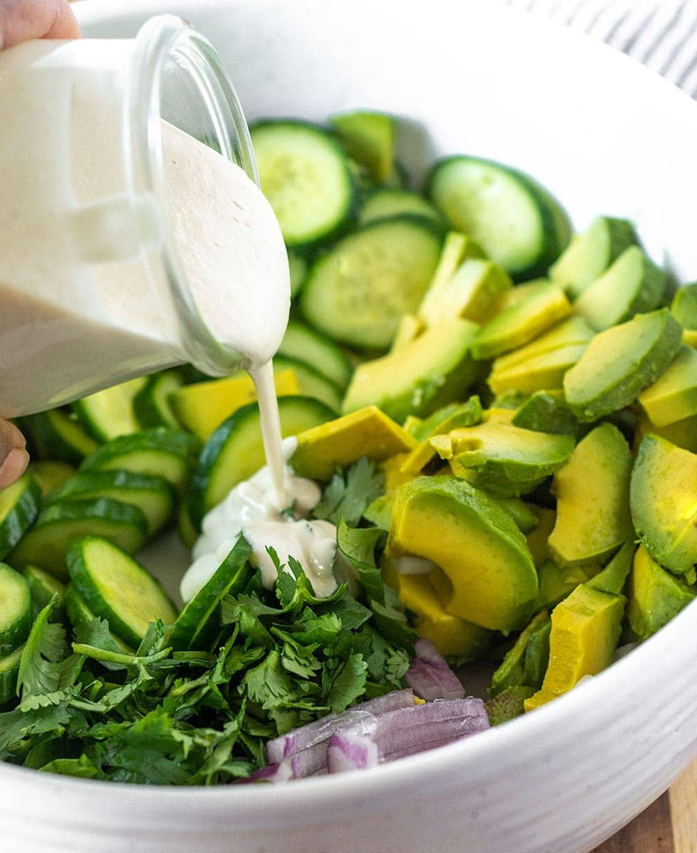 Cucumber avocado salad with dressing being pooured