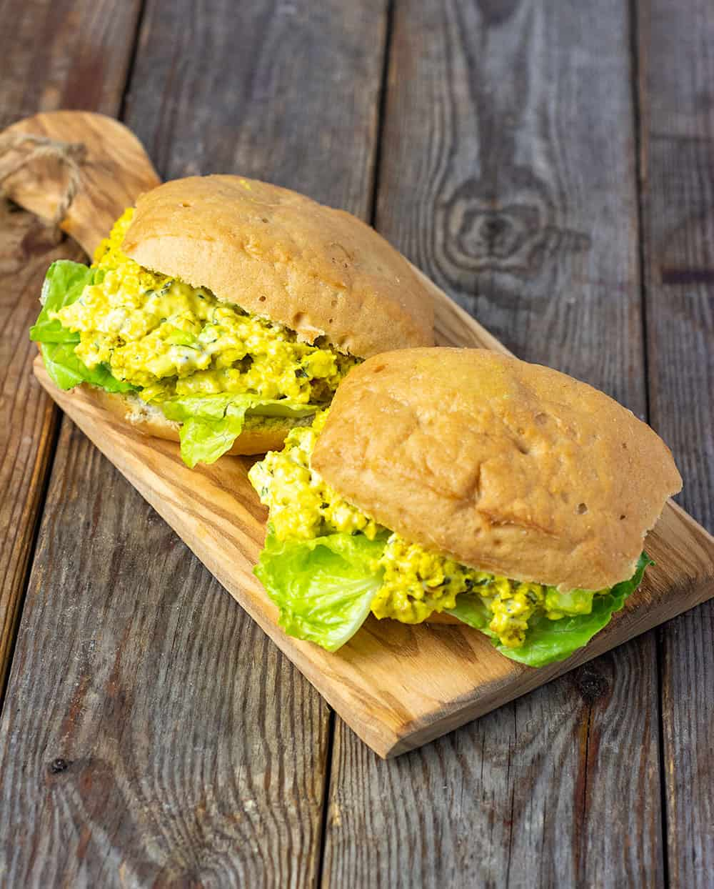 two egg salad sandwiches on a wooden board