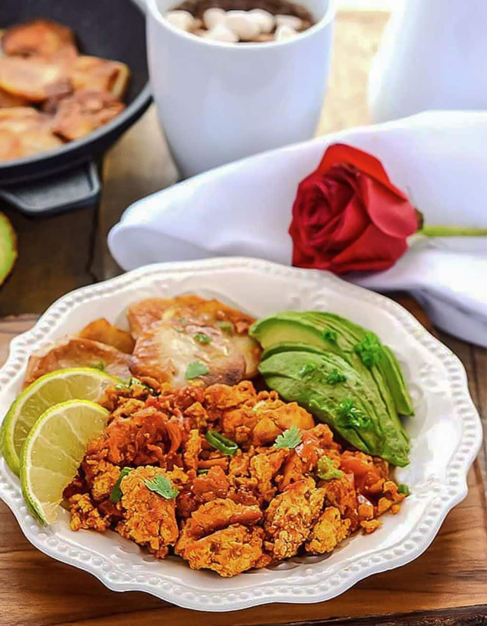 Scrambled tofu mexican-style using tex-mex herbs and spices, served with fried potatoes, avocado and garnished with cilantro and lime slices on a white plate, on a wooden background with a white napkin in the background with a red rose and lime