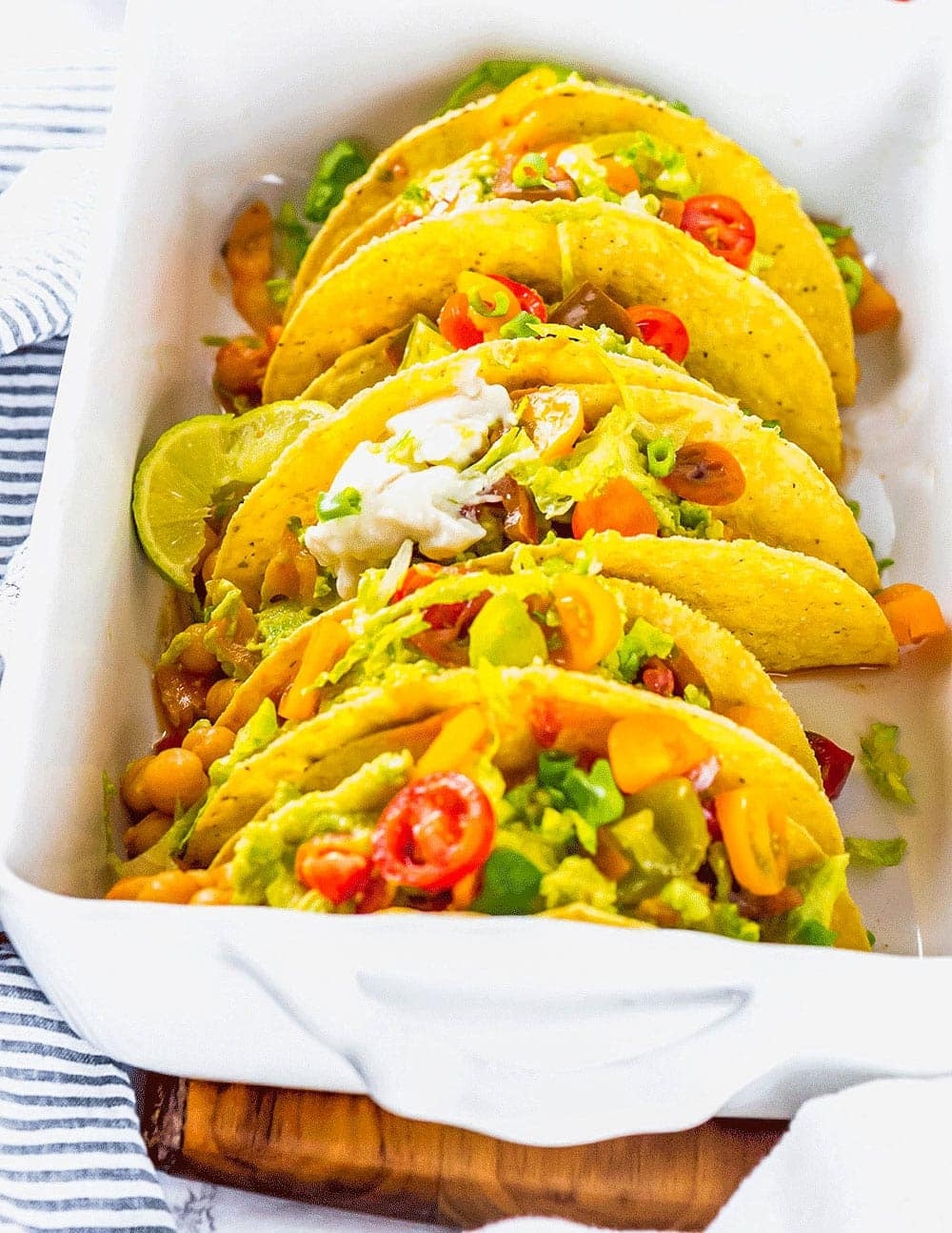 Easy Chickpea Tacos with chickpea stew topped with guacamole, tomatoes, sour cream lettuce in a white casserole dish