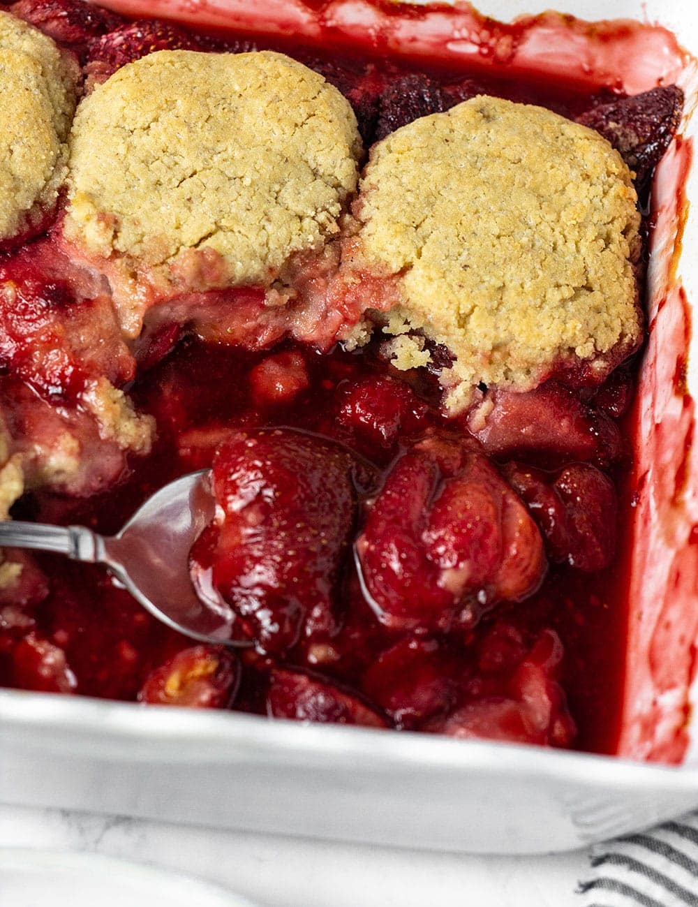 Close up view of strawberry cobbler being served with a spoon