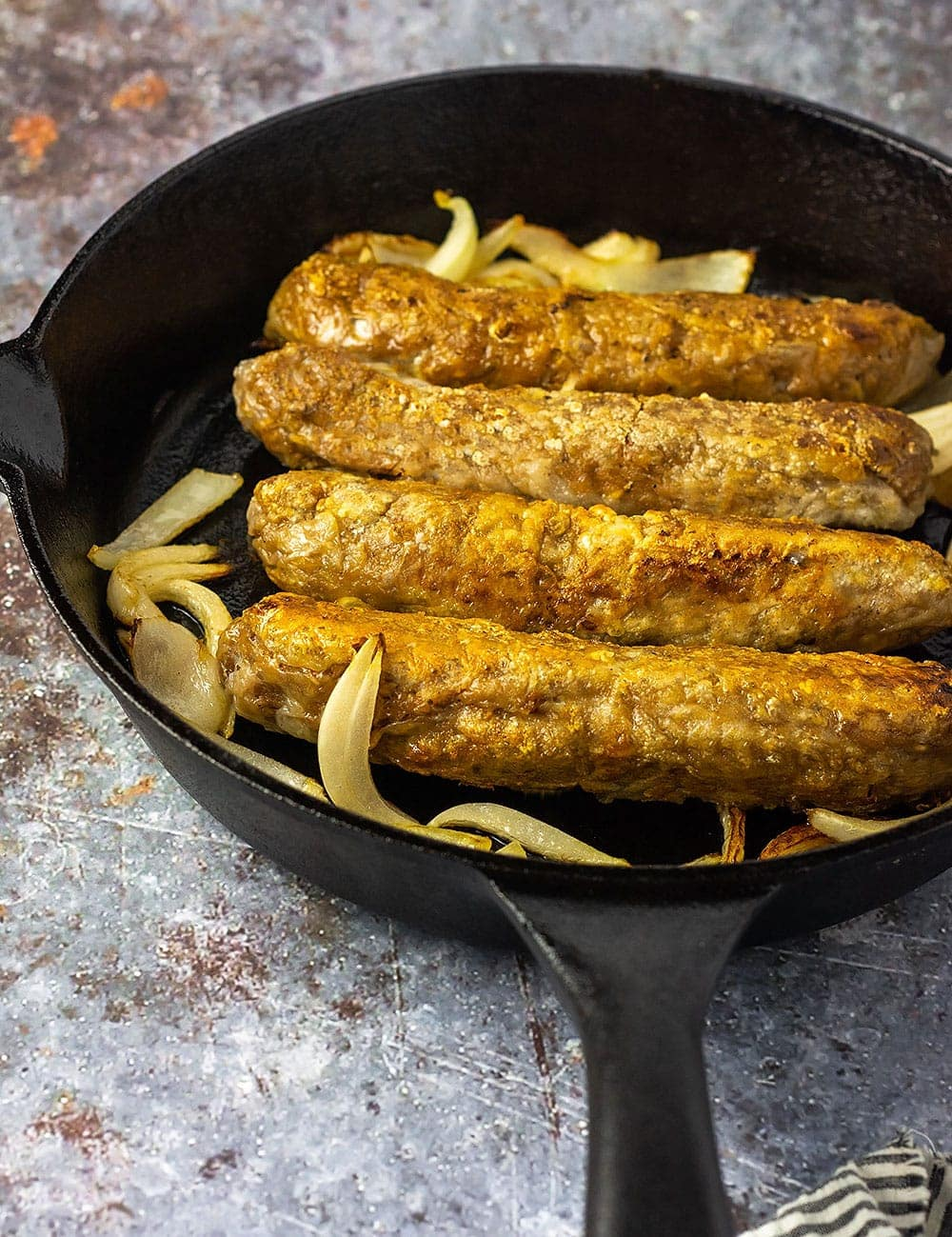 Vegan and gluten-free sausage in skillet with sauteed onions on a marbled background