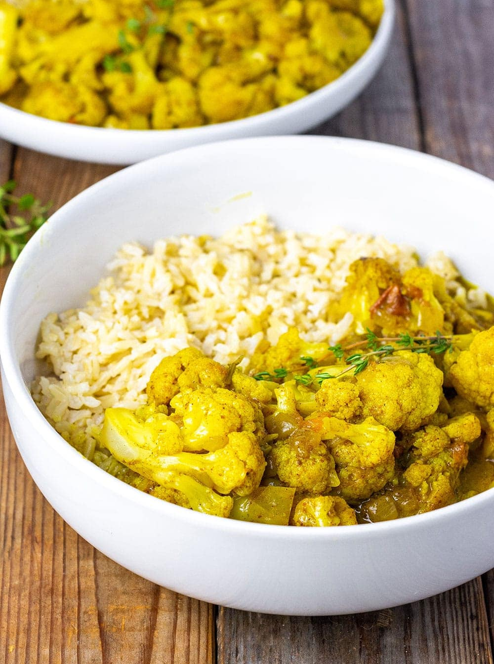 Cauliflower curry with brown rice in a white bowl on a wooden background