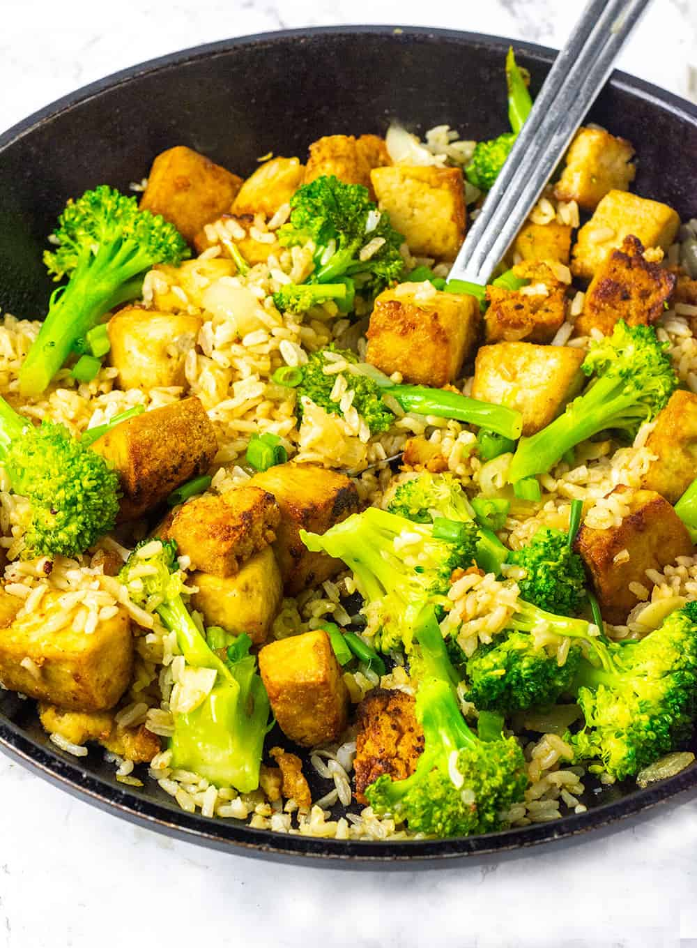 Marinated tofu fried rice with broccoli and seasoned tofu in a skillet