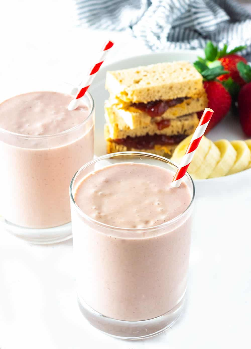two glasses of pbj smoothie with red and white straws, and pbj sandwiches, strawberries, and banana in the background