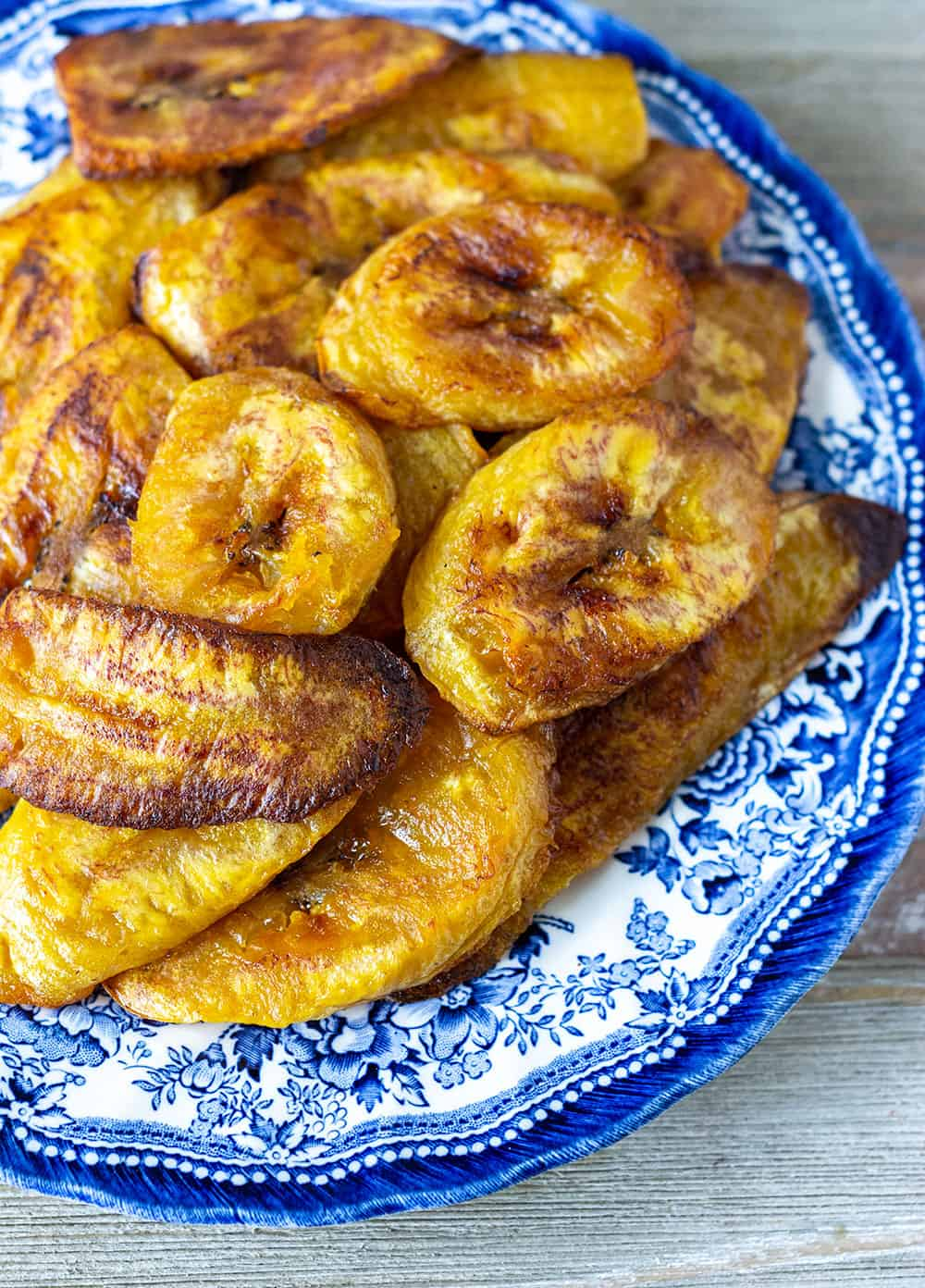 pile of baked plantains on blue and white plate