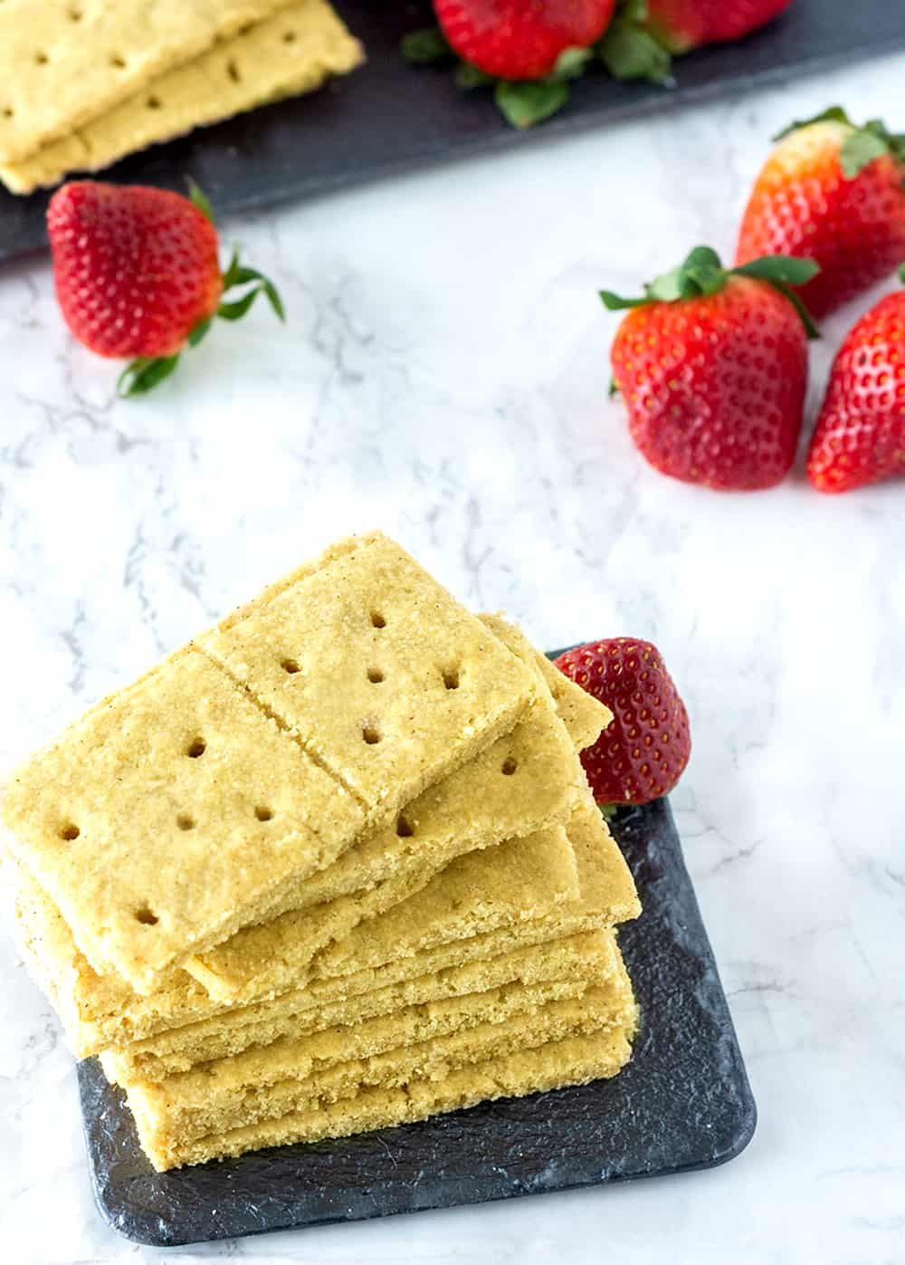 a stack of gluten-free vegan Graham cracker placed next to some strawberries