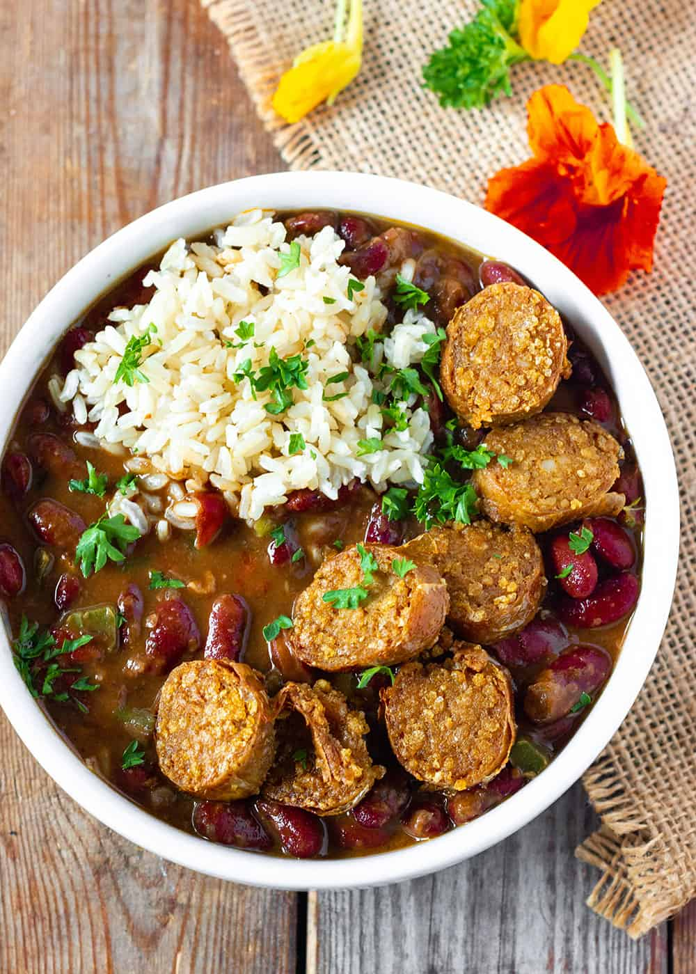rice smothered with red beans with slices of vegan sausage in a white bowl