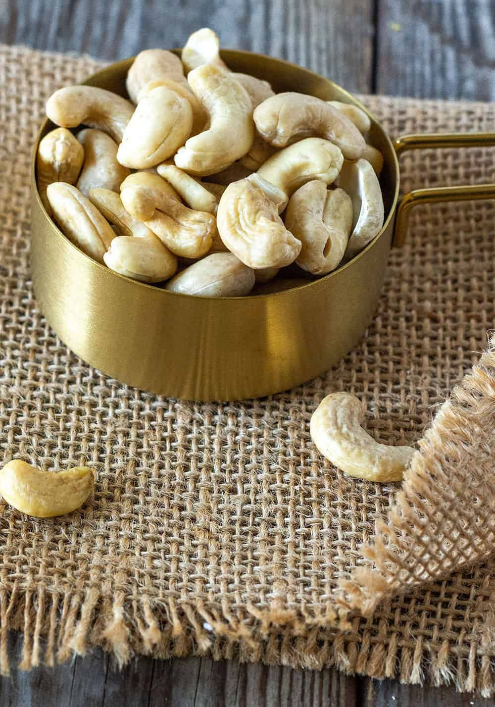 Whole cashews for cashew cream recipe in a gold measuring cup on a brown burlap napkin on a wooden board