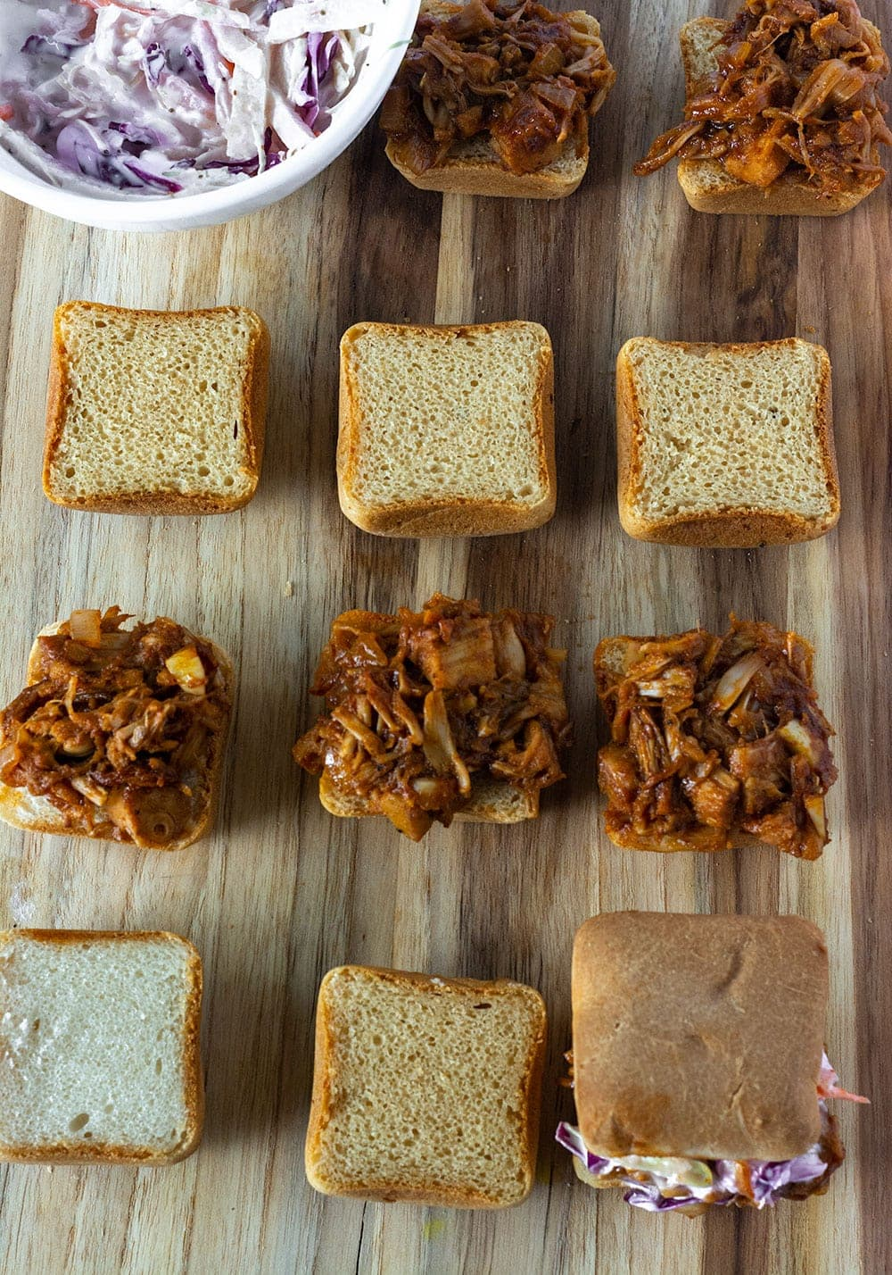 Jackfruit BBQ Sandwiches being assembled on cutting board with pulled jackfruit, rolls and coleslaw