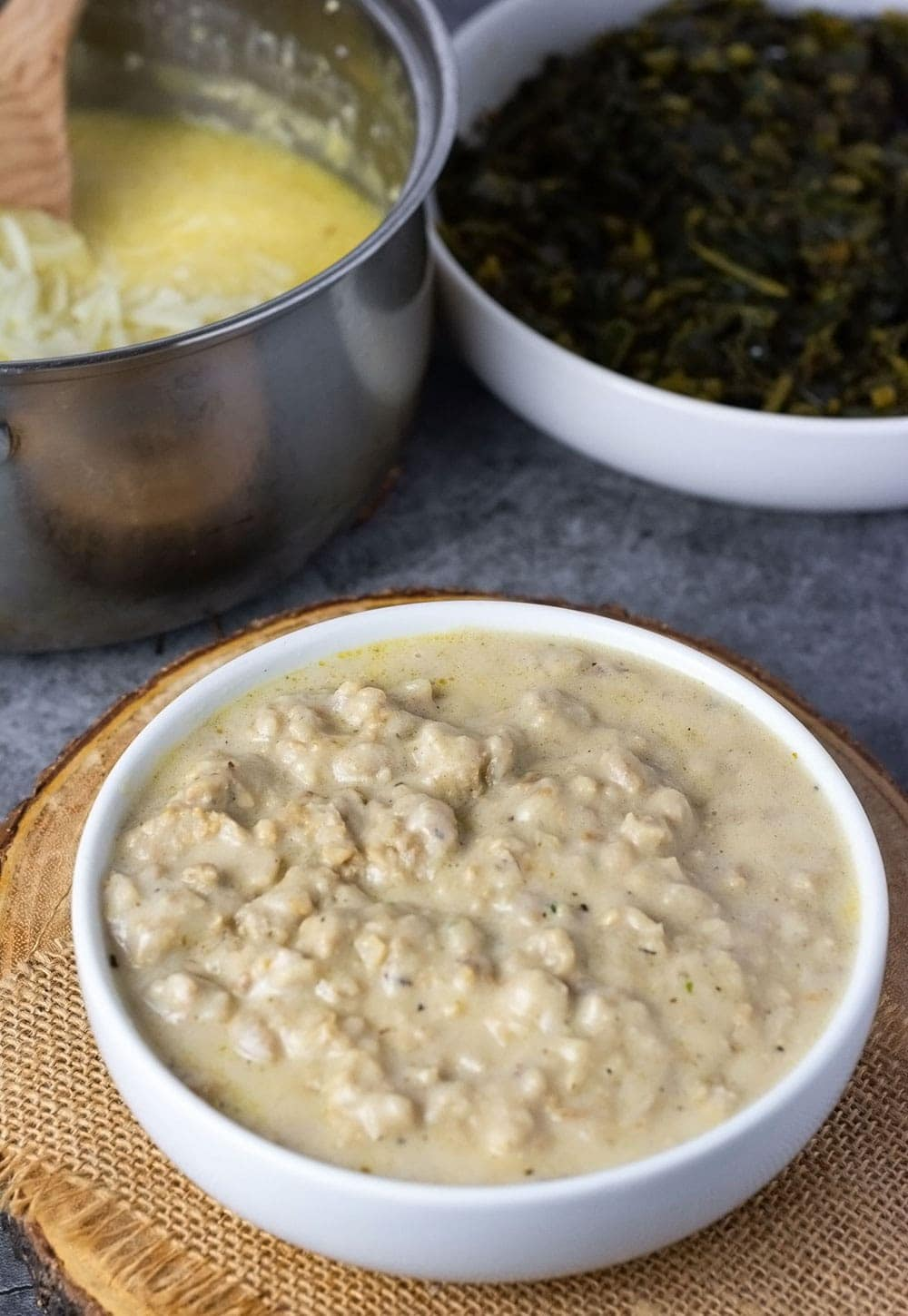 Overlay of vegan sausage gravy in a white bowl on w wooden background, white bowl with collard greens and a pot of grits
