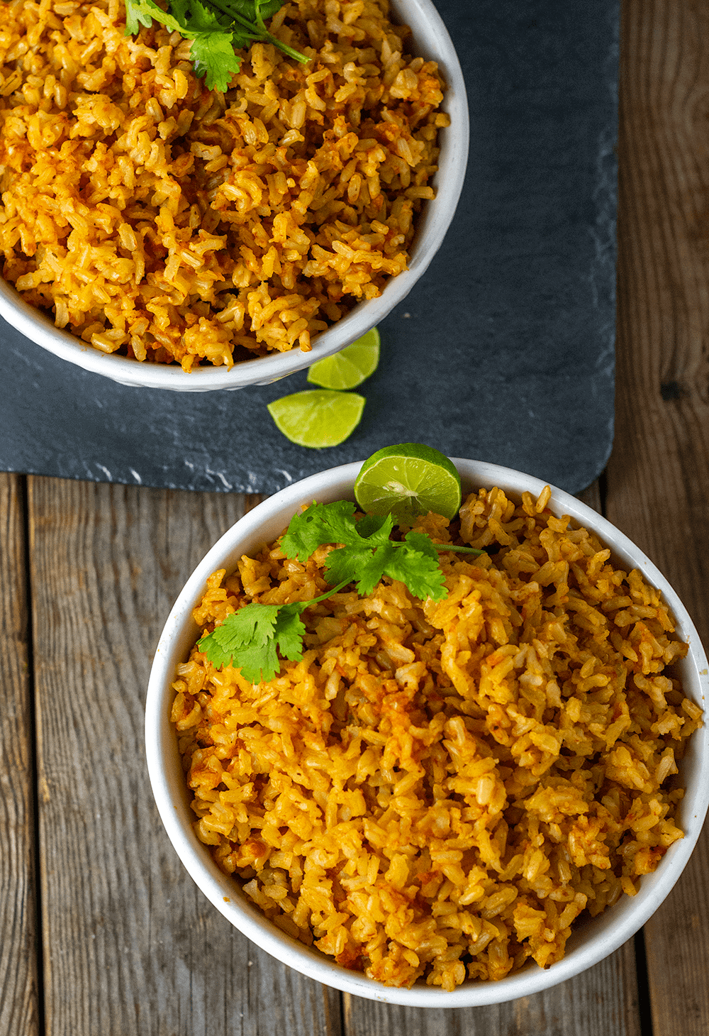 Instant Pot Mexican Rice overlay of rice in two white bowls garnished with lime and cilantro on a wooden background