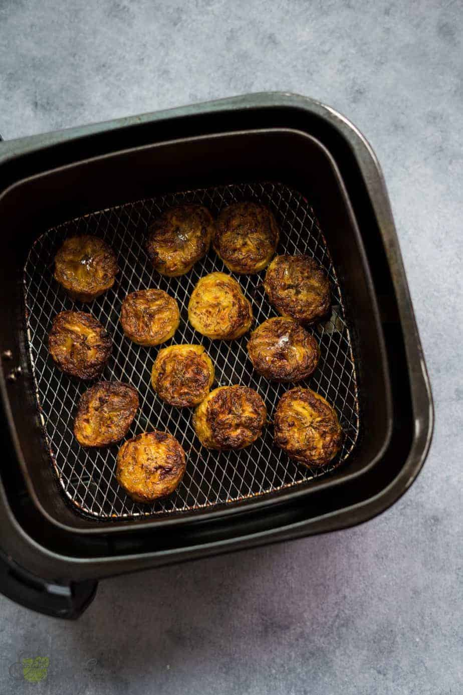 freshly fried plantains air fryer in the basket basket. with a golden brown color and crispy texture in the outside and soft and sweet inside.