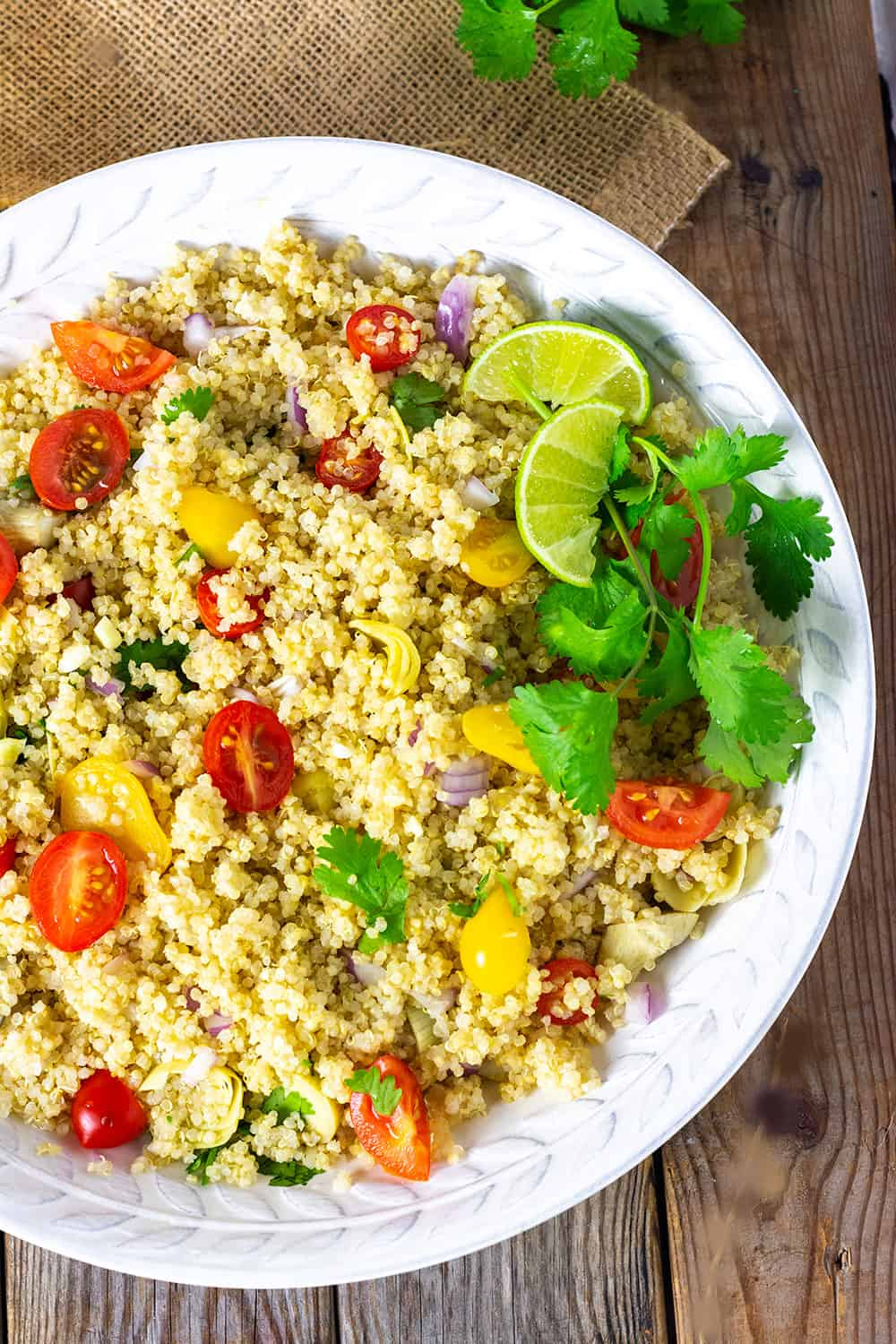 Easy Quinoa Salad With Artichokes in a large white bowl and garnished with cilantro and lime wedges