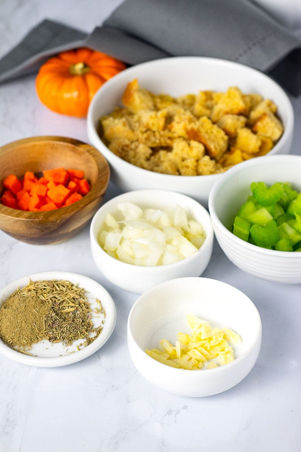Ingredients for homemade cornbread stuffing in white bowls on a white marble background