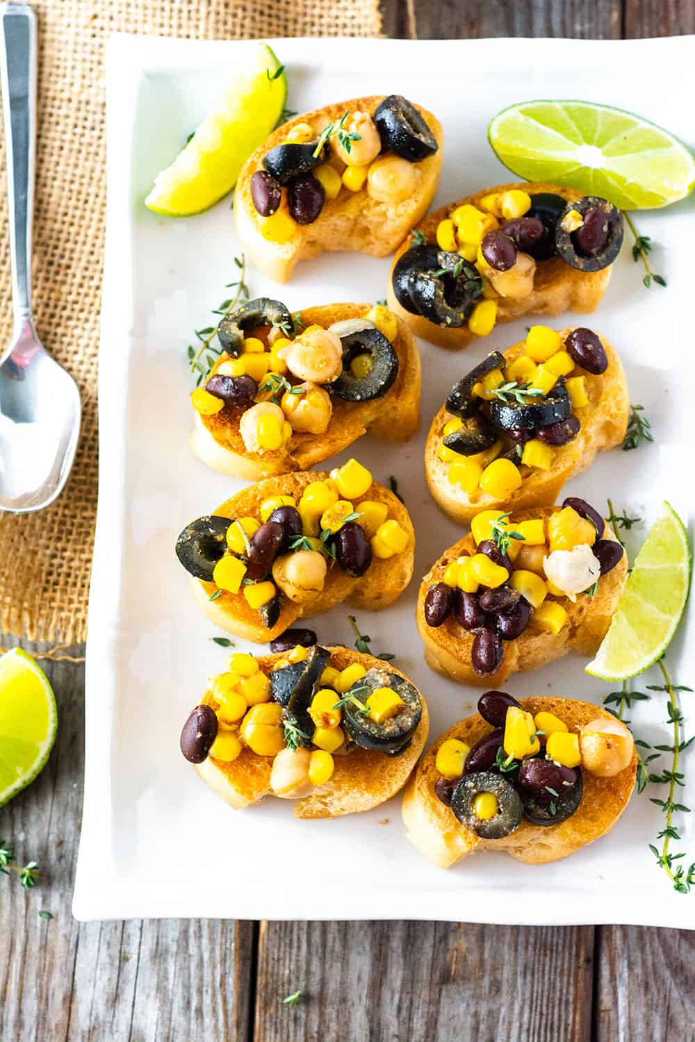 Chickpea Salad Crostini white platter overlay photo with crostini toasts topped with black beans, chickpea, corn., black olives and garnished with thyme and lime slices