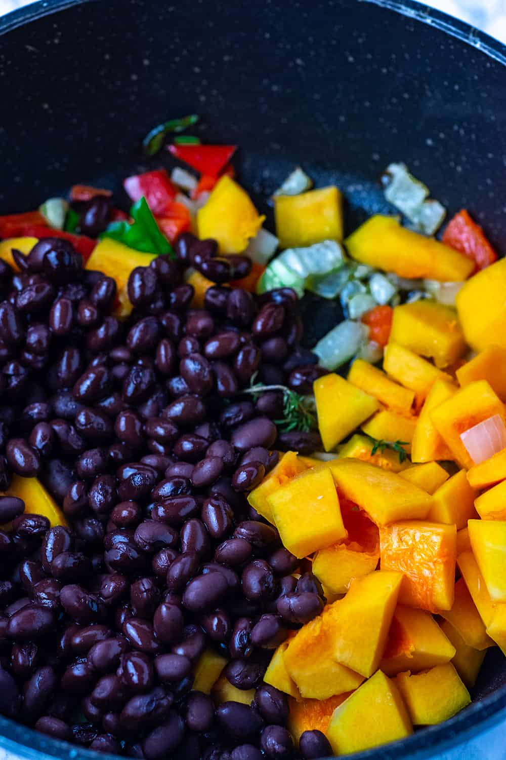 Ingredients for black bean and butternut squash stew, black bean, onion, garlic, bell pepper in a black saucepan
