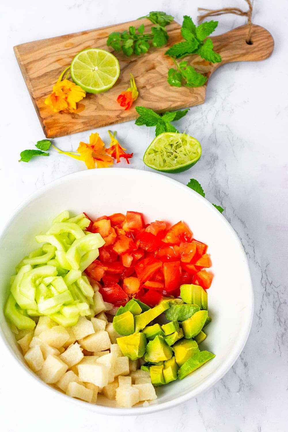 Jicama salad overlay with ingredients in a bowl, cubed jicama, tomato, cucumber and avocado with cutting board in the background with herbs
