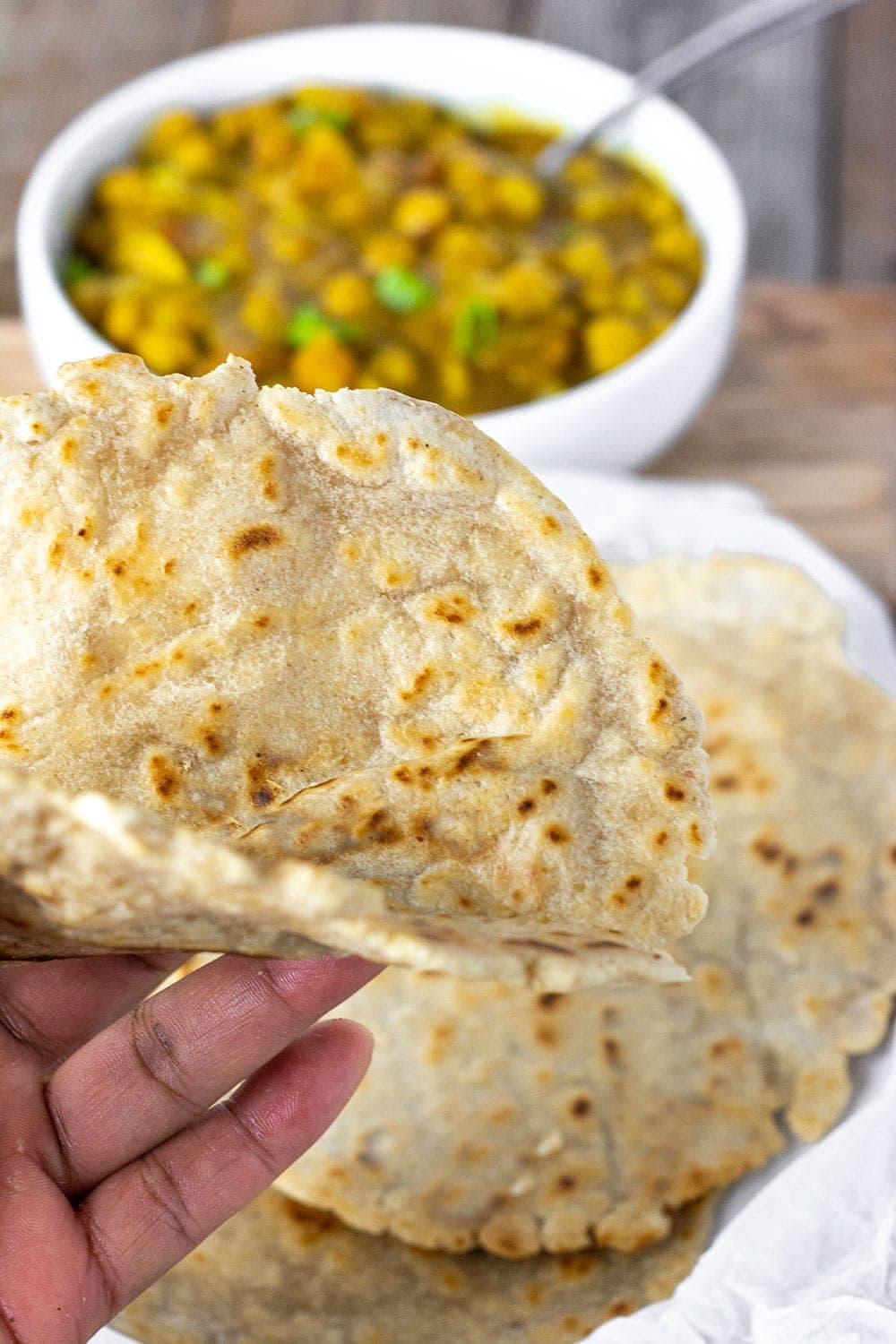 gluten-free flatbread being folded in hand above white plate with more flatbread and chickpea curry in the background