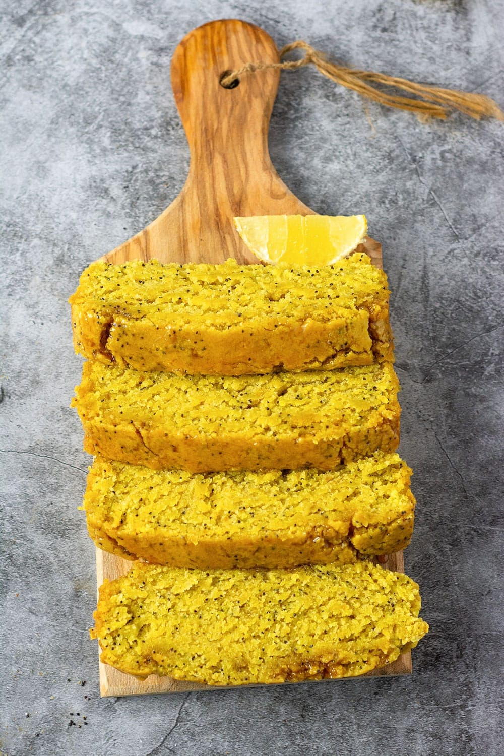 Overlay Lemon Poppy Seed Bread Vegan Gluten-free on a cutting board with lemon slices on a grey background