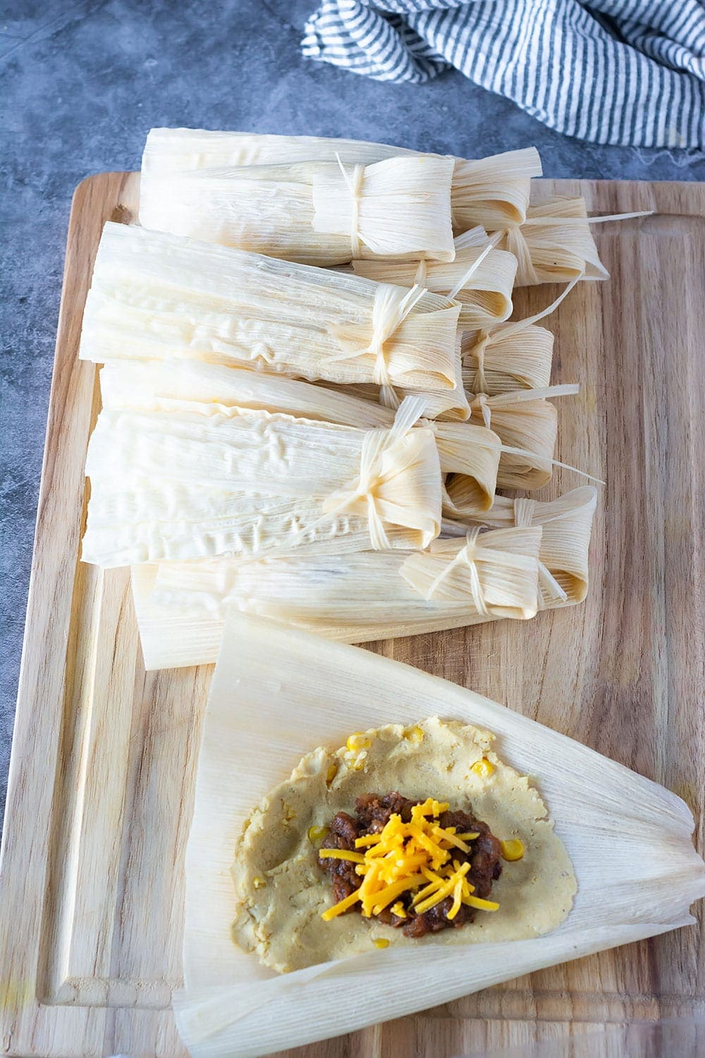 Making tamales, tamales in corn husks on a cutting board