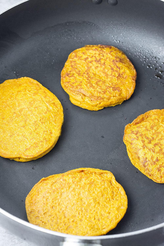 vegan pumpkin pancakes in the skillet being cooked