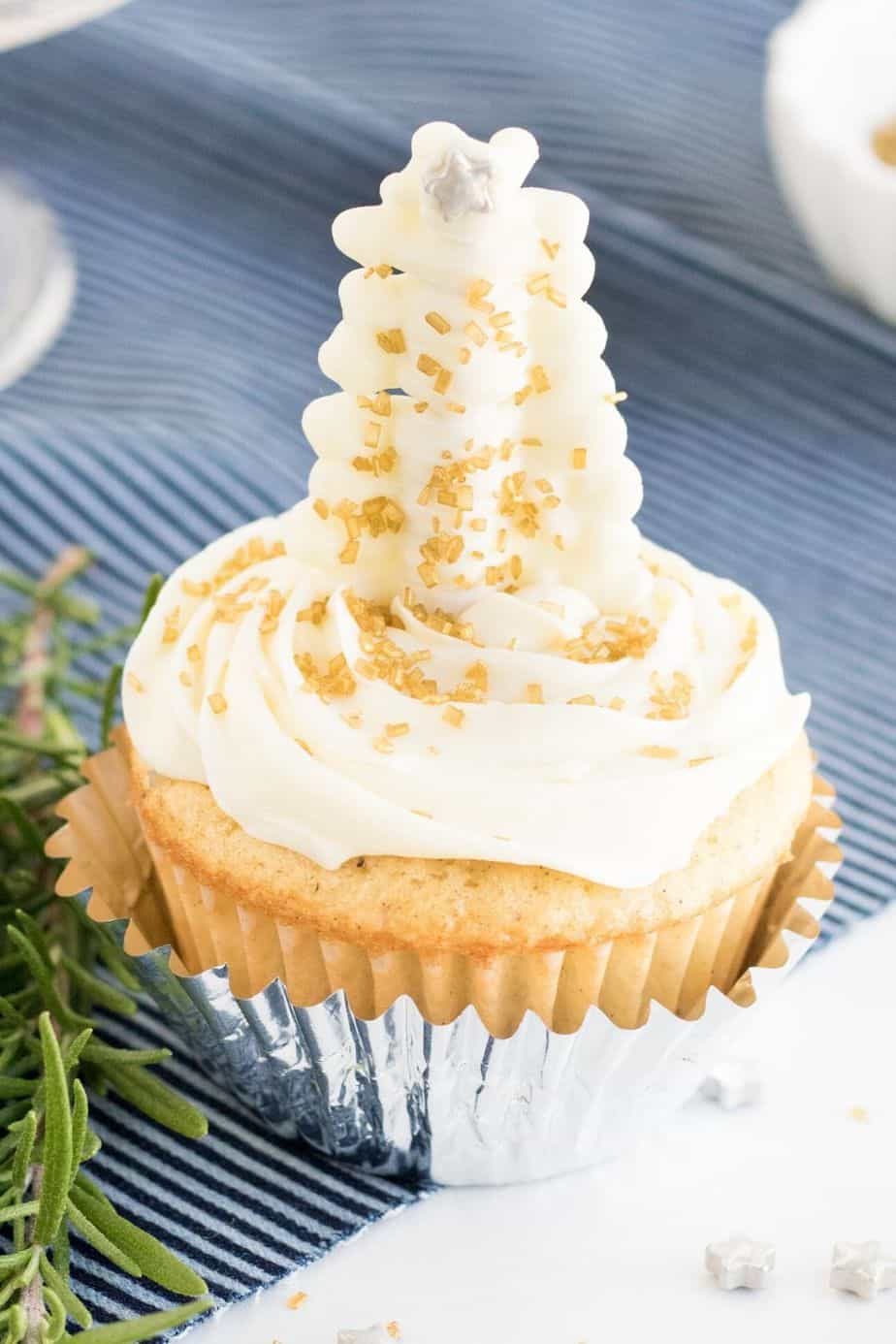 Satisfy your yuletide sweet tooth with these elegant Christmas Tree Cupcakes. This easy Christmas dessert recipe is perfect for your holiday spread. White Chocolate and pretzel sticks make the pretty glittering Christmas tree topper. #christmascupcake #cupcakerecipe #dessert