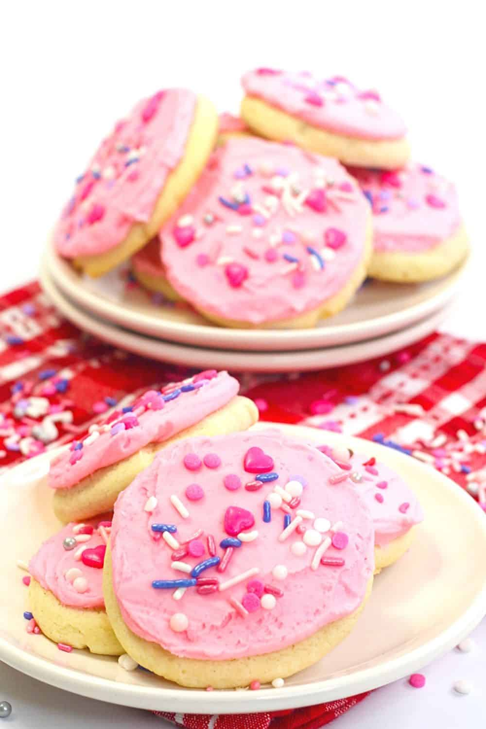 These soft and buttery Valentine Lofthouse Sugar Cookies are the perfect sweet treat. These sour cream cookies are topped with sweet frosting and sprinkles. #sugarcookies #lofthousecookies #valentinesdayrecipe #partyidea