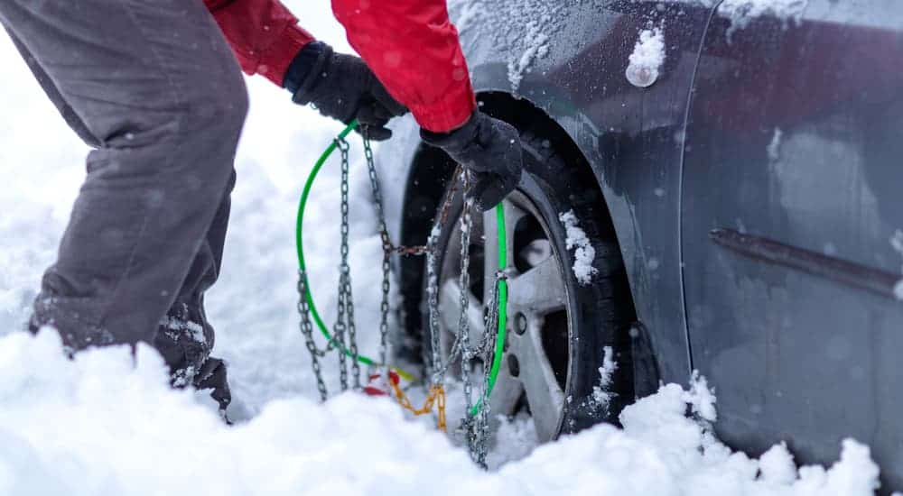 A man is putting tire chains on his car in the snow.