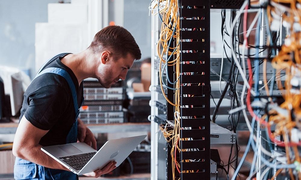 Junger Mann mit Laptop arbeitet an Servern und Kabeln im Serverraum.
