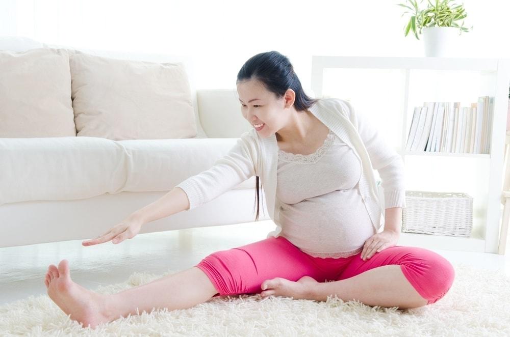 Mujer embarazada que se estira tratando de prevenir calambres del músculo