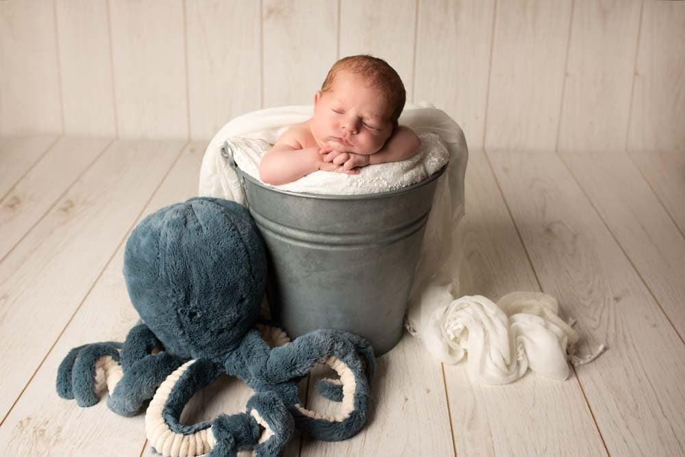 Newborn Baby in a bucket with octopus for first photoshoot