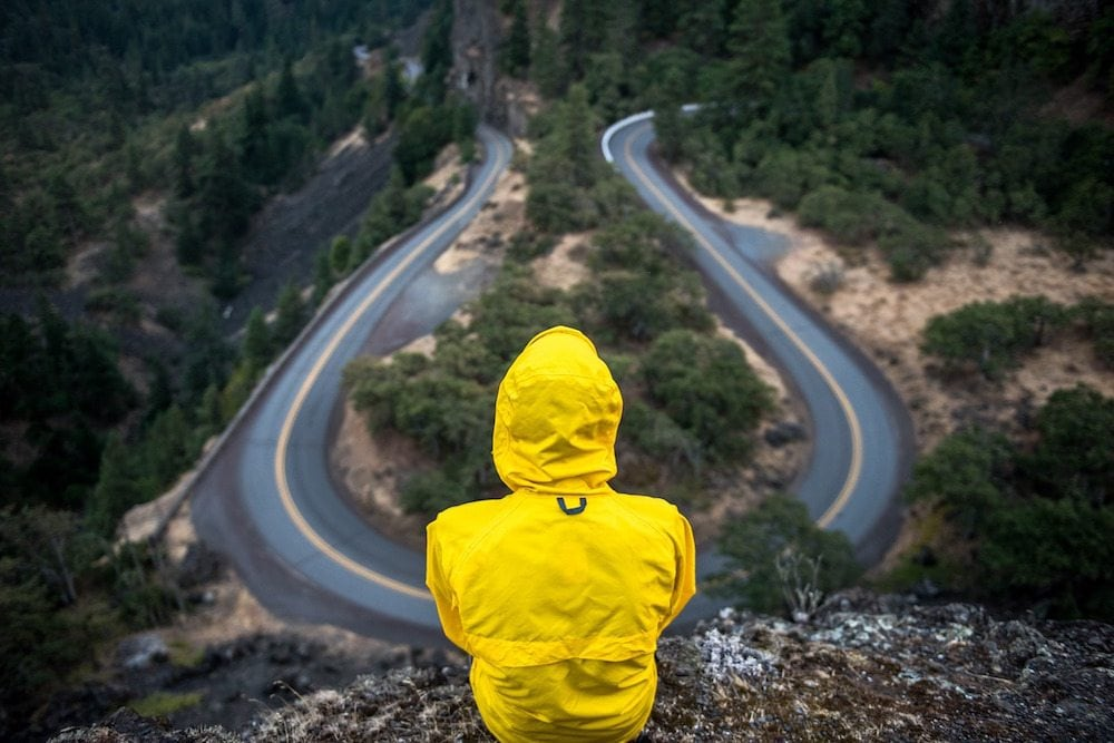 Image: Person siting above a winding road looking down at it