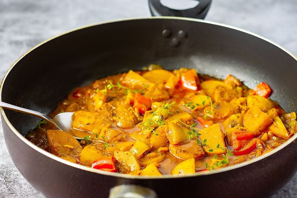 Turnip curry cook with bell pepper, curry spice, turmeric, thyme in a black saucepan on a grey background