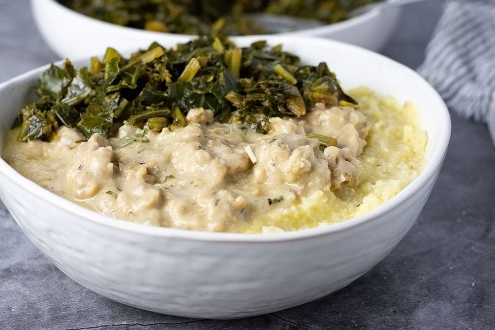 Close up vegan sausage gravy in a bowl with grits and collards green