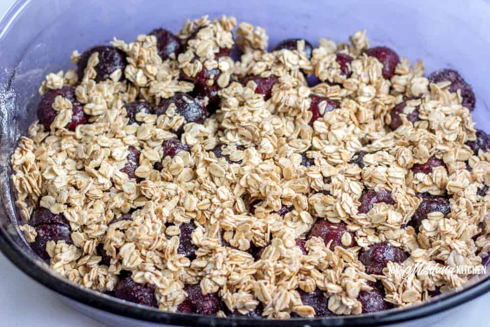 Sweet cherries topped with an easy oatmeal crust. This Cherry Crisp Recipe is easy to make and is a great way to use frozen cherries for a delicious Trim Healthy Mama E Dessert. #trimhealtheymama #thm #thme #lowfat #healthycarbs #cherries #crisp #thmedessert #thmdessert #trimhealthymamaefuel #mymontanakitchen #nosugaradded #dairyfree #glutenfree
