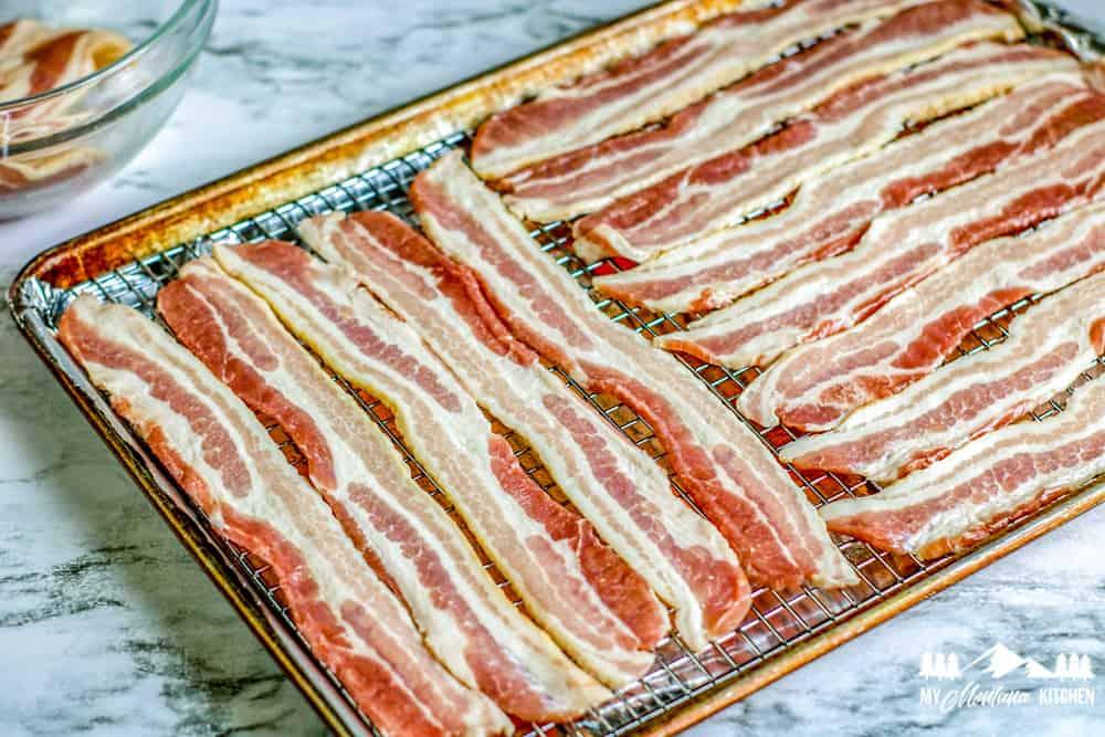 raw bacon on baking sheet