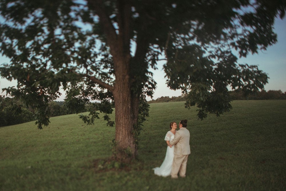 bride and groom embracing under tree