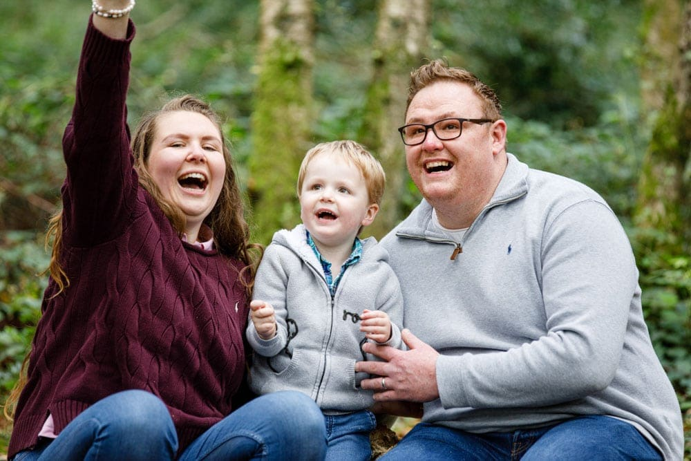 Family laughing whilst on a tree in the woods