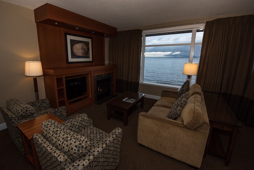 Living room with TV, fireplace, plenty of seating and large open windows looking out over the water.