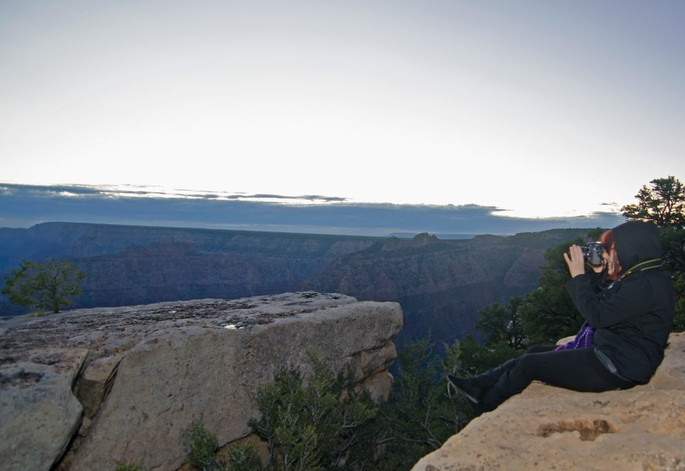 Brooke sitting on the edge of the Grand Canyon taking a photo