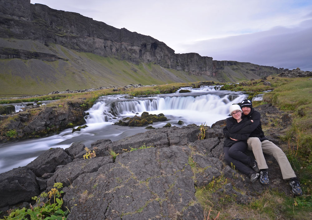 Brooke and Buddy sitting next to a road-side waterfall during their Iceland Vacation