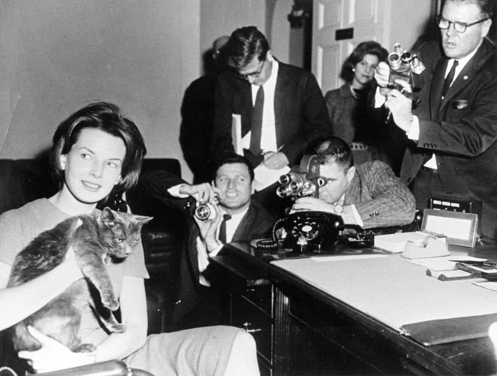 First Lady Jacqueline Kennedy's Press Secretary Pamela Turnure sits in an office holding Caroline Kennedy's cat, Tom Kitten, 24 January, 1961.  Photo: Abbie Rowe. White House Photographs. John F. Kennedy Presidential Library and Museum, Boston, public domain.